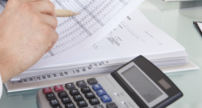 Cropped image of businessman calculating expense at desk in office